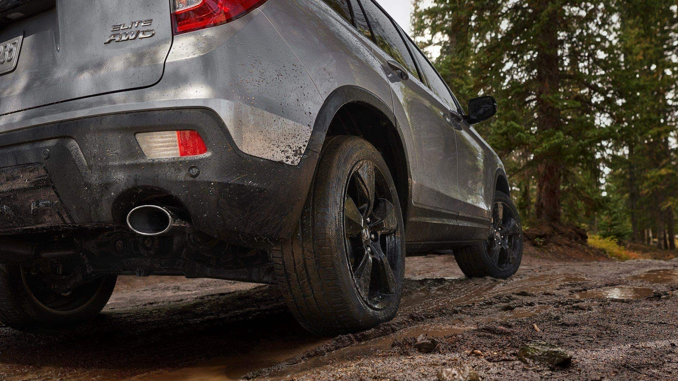 Passenger-side 3/4 view of 2019 Honda Passport Elite in Lunar Silver Metallic demonstrating all-season tires covered in mud on rocky terrain.