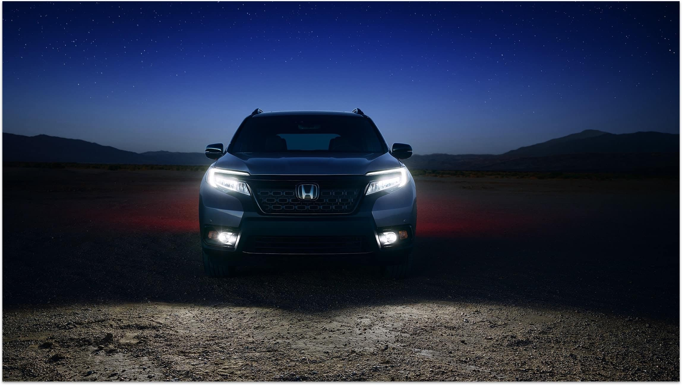 Direct front view of 2019 Honda Passport Elite in Modern Steel Metallic with LED low-beam headlights and fog lights on.
