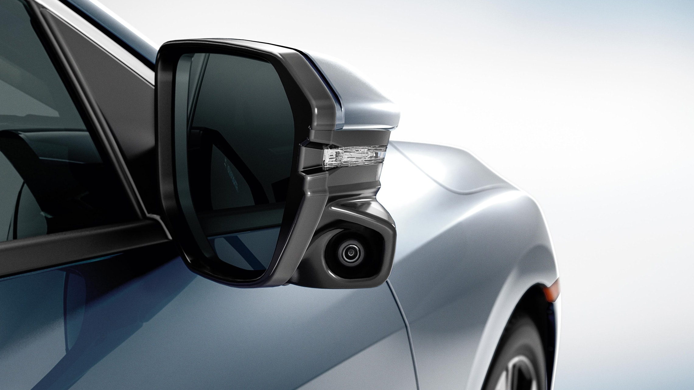 Detail of Honda LaneWatch™ camera on passenger-side rear view mirror of the 2020 Honda Civic Touring Coupe.